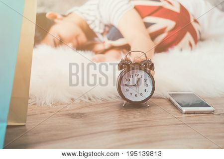 Happy young asian woman waking up and turning off the alarm clock having a good day