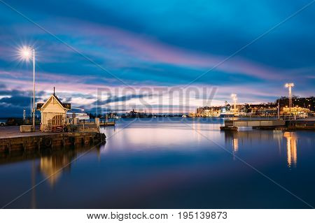 Helsinki, Finland. Landscape With City Pier, Jetty At Winter Sunrise Or Sunset Time.  Blue Sky Reflected In Tranquil Sea Water Surface. Berth In Lighting At Evening Or Night Illumination.
