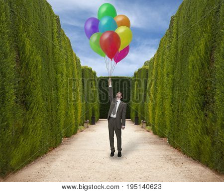 Businessman in the park holds the inflated balloons