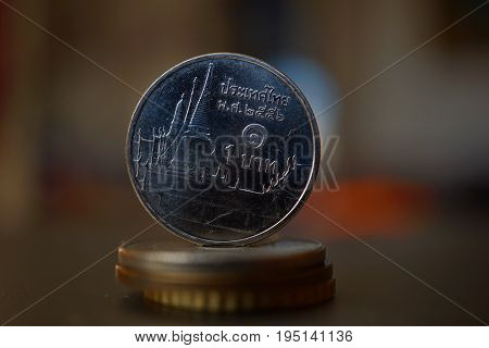 Macro detail of a Thai coin (Thai baht, THB) on the top of column created of coins with a positive colorful warm background