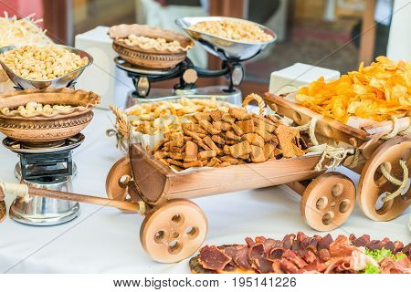 Crackers and chips in a small decorative wooden cart and nuts on the weight