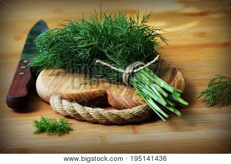 Fresh organic dill for cook put on wooden cutting board with knife .