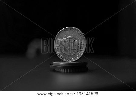 Macro detail in black and white of an American coin (five cents of American dollar, USD) on the top of column created of coins with a negative dark background