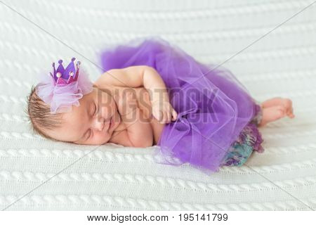 Portrait of newborn baby girl princess with crown sleeping on soft white blanket.