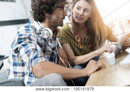 Trendy people in office lounge websurfing on tablet