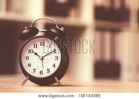 Classic alarm clock showing time during working hours or work break in business office retro toned image with selective focus