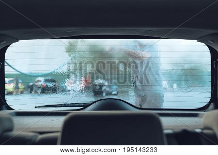 Man washing car in self-service car wash station viewed from inside of the vehicle selective focus