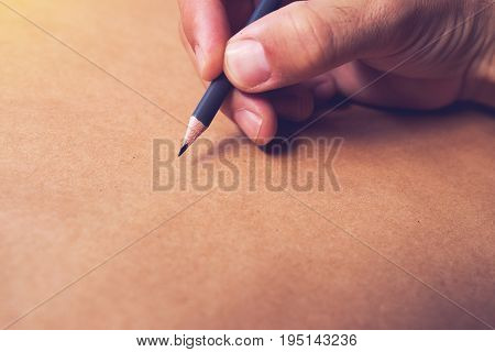 Male illustrator and sketch artist drawing with pencil hand close up with selective focus