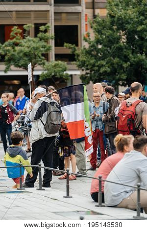 STRASBOURG FRANCE - JUL 12 2017: French flag with protesters in city as Melenchon called for day of protest against Macron government spending cuts and pro-business tax and labor reforms