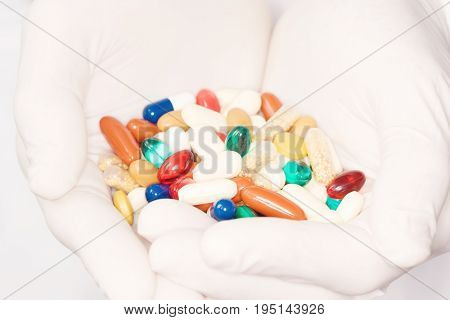 Closeup of pharmacist holding handful of colorful pills