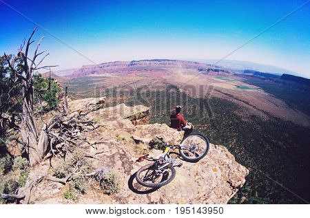 High angle view of mountain biker on rock looking at view