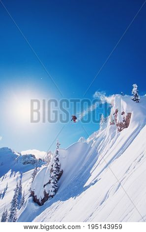 Skier jumping from mountain ledge against clear sky