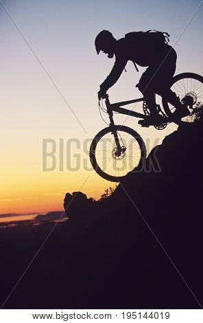 Silhouette image of mountain biker riding down slope