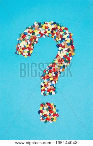 Various pills forming question mark, on blue background
