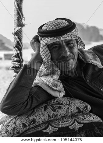 Wadi Rum Jordan - June 20 2017: Bedouin man or Arab man in traditional outfit lying down on the couch desert background.