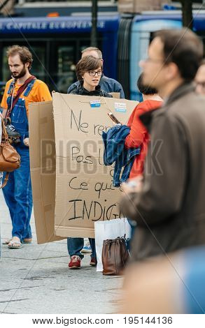 STRASBOURG FRANCE - JUL 12 2017: Woman wearing placard at protest against Macron government spending cuts and pro-business tax and labor reforms