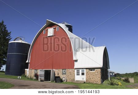 Vintage red bard with a metal roof against a blue sky