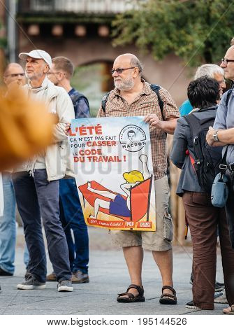 STRASBOURG FRANCE - JUL 12 2017: Senior man with placard in Place Kleber as Melenchon called for day of protest against Macron government spending cuts and pro-business tax and labor reforms