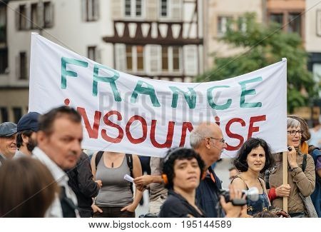 STRASBOURG FRANCE - JUL 12 2017: France Insoumise placard at protest against Macron government spending cuts and pro-business tax and labor reforms