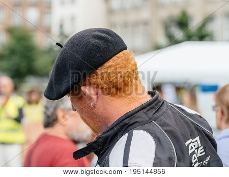 STRASBOURG FRANCE - JUL 12 2017: Redhead man wearing French hat at protest against Macron government spending cuts and pro-business tax and labor reforms