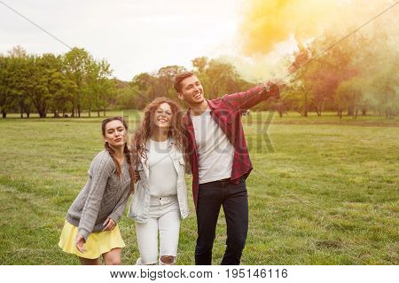 Group of three youngsters posing on meadow in park holding colored smoke bomb.