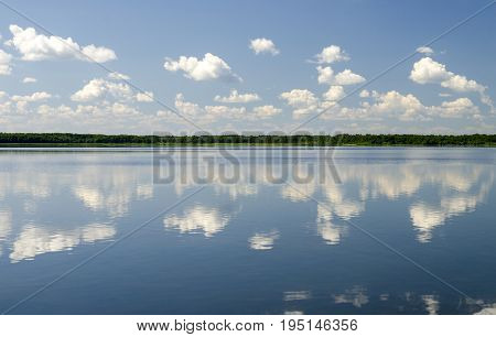 Pure summer lake background clouds reflect in the pure water of a lake