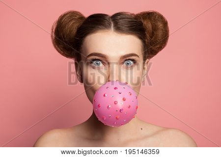 Portrait of model with two buns blowing gum bubble on pink background.