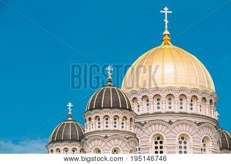 Riga, Latvia. Riga Nativity Of Christ Cathedral - Famous Church And Landmark. Close Up Of Golden Yellow Domes On Blue Sunny Sky Background At Summer Season