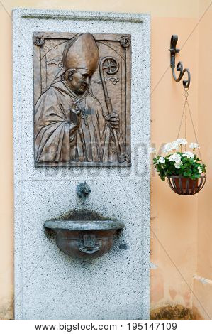 Tape in bronze of the Pope Jean-Paul two hang on a plate of granite with a sink and a pot of flowers