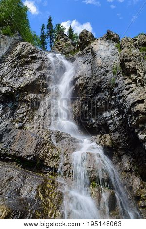 Shirlak waterfall in rocks on blue sky with white clouds background. Tektu river Altai Mountains Altay Republic Siberia Russia. Vertical orientation.