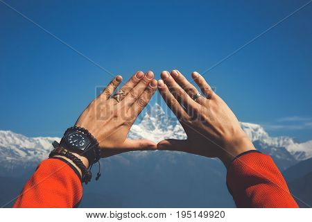 Hands framing the snowy mountain peak. Mt. Machapuchare (6,993 m)  in the center (Nepal, Himalayas). poster