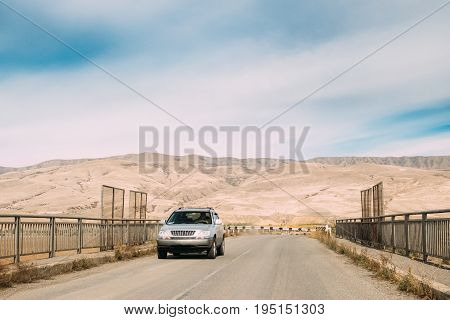 Gori, Shida Kartli Region, Georgia. SUV Car On Country Road In On Autumn Landscape Background Of Kartli Valley.