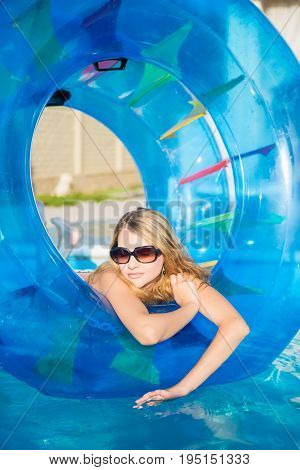 Nice blond woman posing with rubber ring in swimming pool