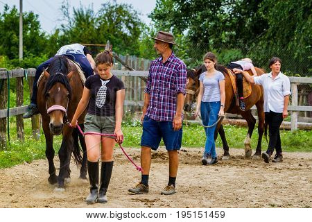 Vynohradiv Ukraine - July 12 2017: Instructor (c) teaches children to ride on horseback during a vacation in the summer children's equestrian sports camp.