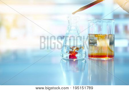 glass flask and beaker in science laboratory with orange drop solution