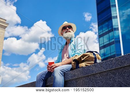 Wide shot of handsome male having rest while drinking coffee and sitting under skyscraper with copy space