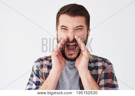 Close-up shot of angry bearded man shouting loudly with hands on the mouth. Emotion, advertisement and people concept