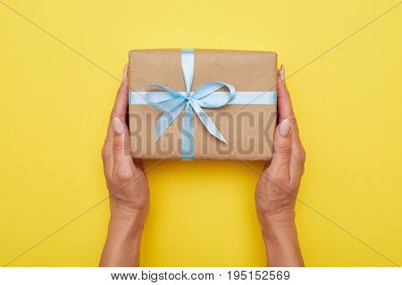 Flat lay of woman hands holding present with box decorated with blue ribbon on yellow background