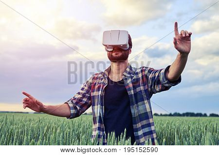Guy using 3D glasses. Holding both hands up, Wearing shirt during early evening on field of weed, mid shot