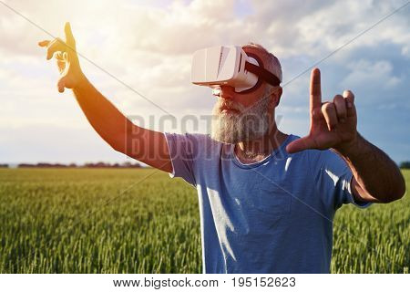 Side view of bearded male in virtual reality, wearing 3D glasses  on  field of weed pointing by fingers