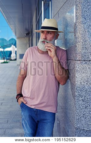 Mid shot of elderly bearded man with electro cigarette wearing casual clothing, standing near wall of building outdoors, looking aside