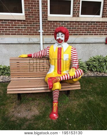 RIVER FALLS,WISCONSIN-JULY 13,2017:The Ronald McDonald mascot sitting on a bench in full makeup.
