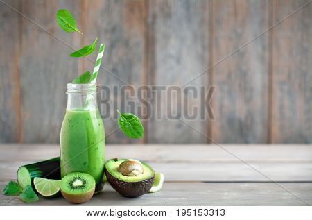 Fresh spinach leaves falling into a green smoothie on a wooden background