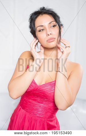 Portrait of pretty thoughtful brunette in pink dress