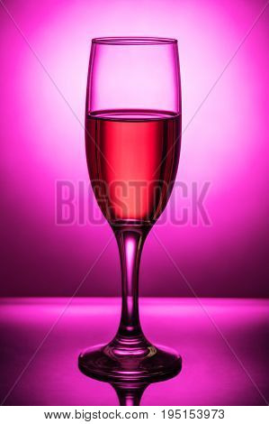 Glass of pink wine shot against the light on the background of the light spot