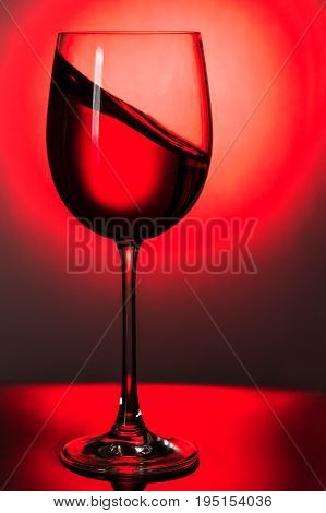 Red wine in a glass with a wave to the side, up to the light