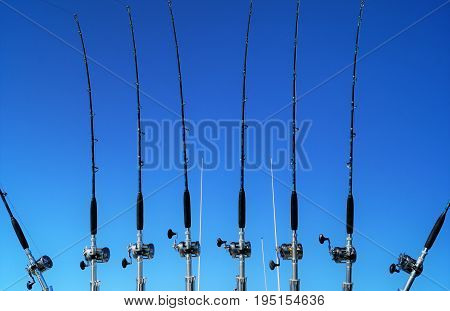 Fishing Rods. A row of fishing rods lined up off the back of a commercial fishing boat