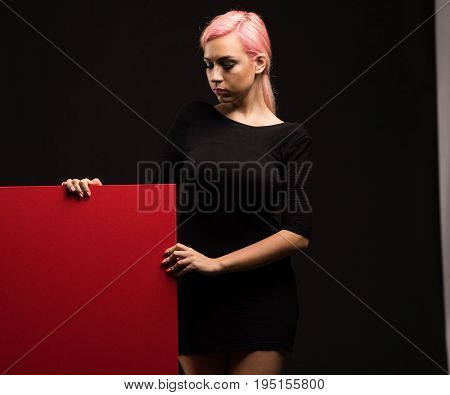 Young wistful woman portrait of a confident businesswoman showing presentation, pointing placard black background. Ideal for banners, registration forms, presentation, landings, presenting concept.