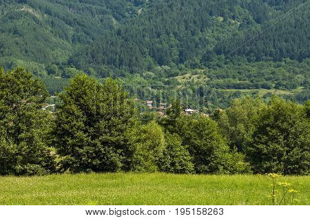 Scene with mountain glade, forest and residential district of bulgarian village Anton, Central Balkan mountain, Stara Planina, Bulgaria