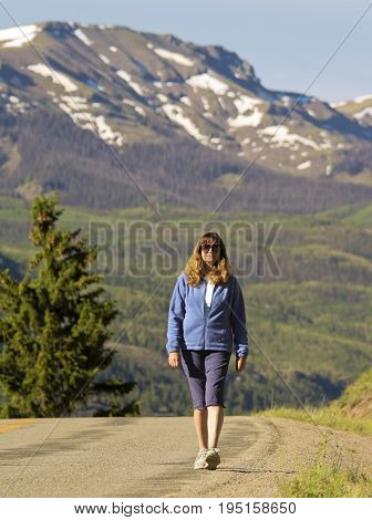 LAKE CITY, COLORADO, JUNE 20. The Alpine Loop Backcountry Byway on June 20, 2017, near Lake City, Colorado. A Woman Walks a Rare Paved Section of the Alpine Loop Backcountry Byway in Colorado.